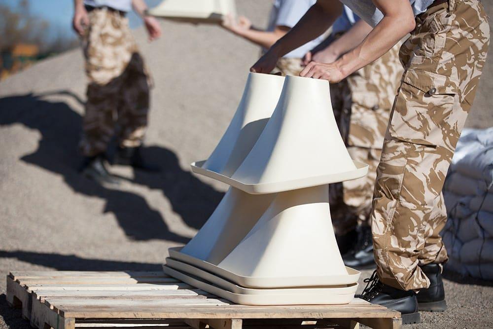 Soldier unloading stack of ExpressBagger funnels for assembly into the ExpressBagger Classic sandbag filling station